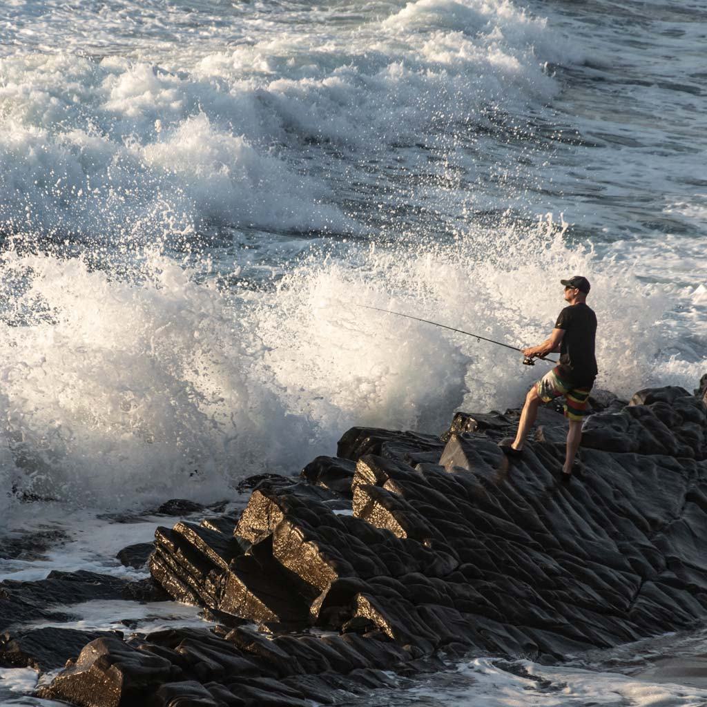 Guy fishing alone in surf off of rocks